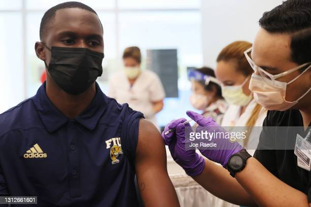 Larry Grier, a junior at Florida International University, receives a Pfizer-BioNtech COVID-19 vaccine from Jason Rodriguez, a pharmacy student, at...
