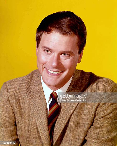 Larry Hagman US actor smiling wearing a brown tweed jacket a white shirt and a striped tie in a studio portrait against a yellow background issued as...