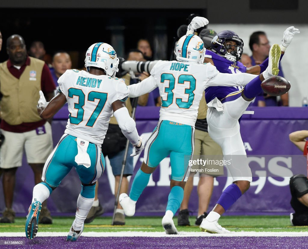 Larry Hope #33 of the Miami Dolphins breaks up a touchdown pass intended for Cayleb Jones #16 of the Minnesota Vikings as teammate A.J. Hendy #37 looks on during the fourth quarter in the preseason game on August 31, 2017 at U.S. Bank Stadium in Minneapolis, Minnesota. The Dolphins defeated the Vikings 30-9.