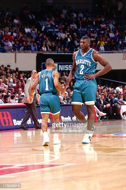 Larry Johnson highfives teammate Muggsy Bogues of the Charlotte Hornets during a game against the New Jersey Nets played circa 1991 at Brendan Byrne...