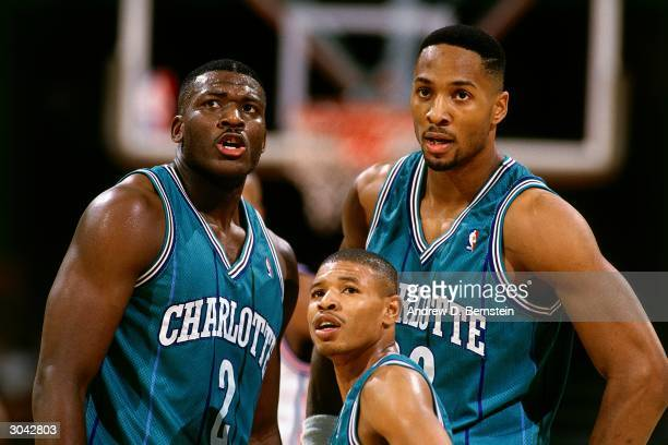 Larry Johnson, 'Mugsy' Bogues and Alonzo Mourning of the Charlotte Hornets take a break during an NBA game circa 1993 at The Charlotte Coliseum in...