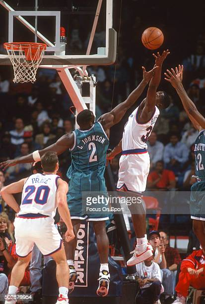 Larry Johnson of the Charlotte Hornets battles for a rebound with Mitchell Butler of the Washington Bullets during an NBA basketball game circa 1993...