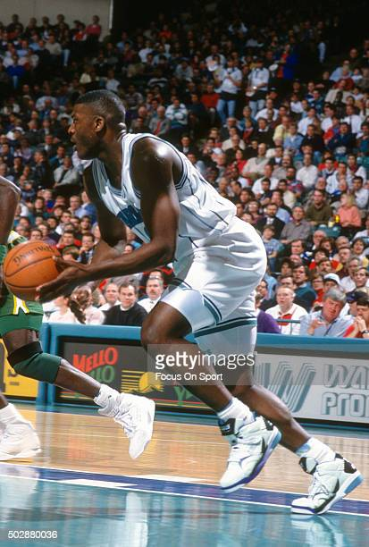 Larry Johnson of the Charlotte Hornets dribbles the ball against the Seattle Supersonics during an NBA basketball game circa 1993 at the Charlotte...
