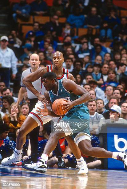 Larry Johnson of the Charlotte Hornets drives on Derrick Coleman of the New Jersey Nets during an NBA basketball game circa 1993 at the Brendan Byrne...