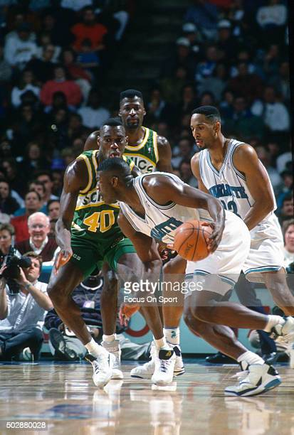 Larry Johnson of the Charlotte Hornets drives on Shawn Kemp of the Seattle Supersonics during an NBA basketball game circa 1993 at the Charlotte...