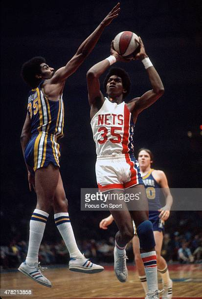 Larry Kenon of the New York Nets goes up to shoot over Roger Brown of the Indiana Pacers during an ABA basketball game circa 1973 at Nassau Veterans...