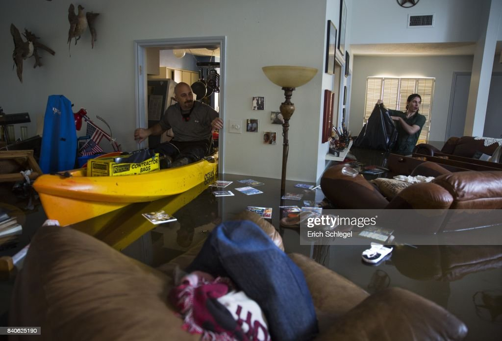 Larry Koser Jr. (L) and his son Matthew look for important papers and heirlooms inside Larry Koser Sr.'s house after it was flooded by heavy rains from Hurricane Harvey August 29, 2017 in the Bear Creek neighborhood of west Houston, Texas. The neighborhood flooded after water was release from nearby Addicks Reservoir.