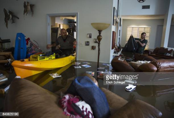 Larry Koser Jr and his son Matthew look for important papers and heirlooms inside Larry Koser Sr's house after it was flooded by heavy rains from...