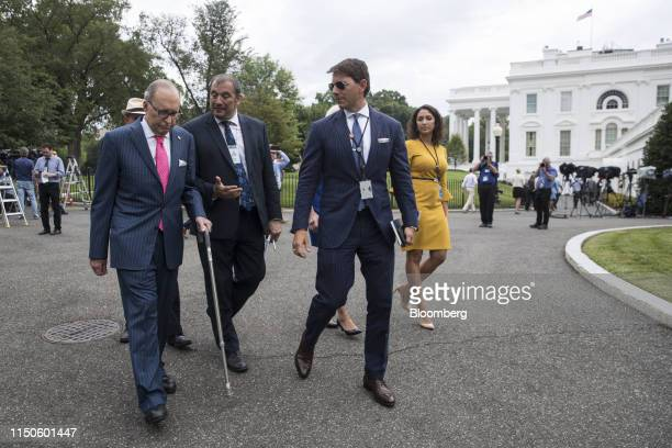 Larry Kudlow director of the US National Economic Council left and Hogan Gidley White House deputy press secretary second right speak with a member...
