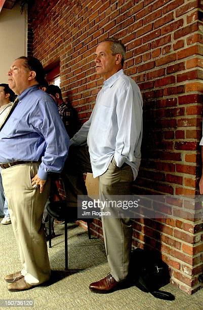 Larry Luchino president and CEO of the Boston Red Sox listens to Ben Cherington general manager of the Boston Red Sox announce a trade between the...