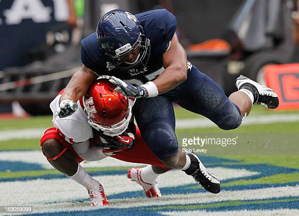 Larry McDuffey of the Houston Cougars collects the pass in his stomach for a touchdown in front of Gabe Baker of the Rice Owls at Reliant Stadium on...
