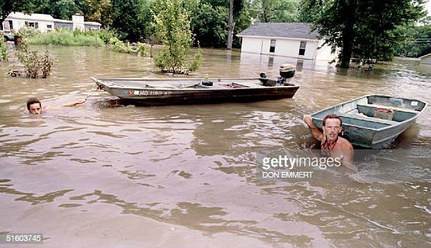 Larry Meyer and Kurt Westmoreland pull their boats through the flooded streets of Portage des Sioux 24 July 1993 After more rain in Missouri Iowa...