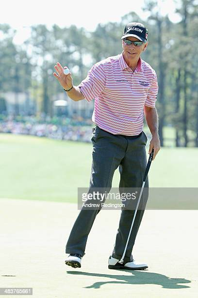 Larry Mize of the United States reacts after sinking a putt on the first hole during the first round of the 2014 Masters Tournament at Augusta...