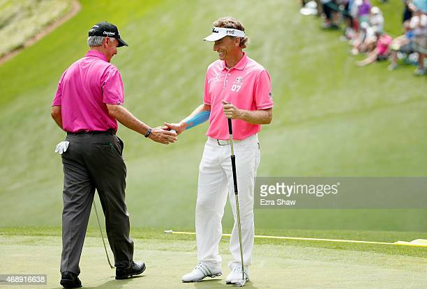 Larry Mize of the United States waits with Bernhard Langer of Germany during the Par 3 Contest prior to the start of the 2015 Masters Tournament at...