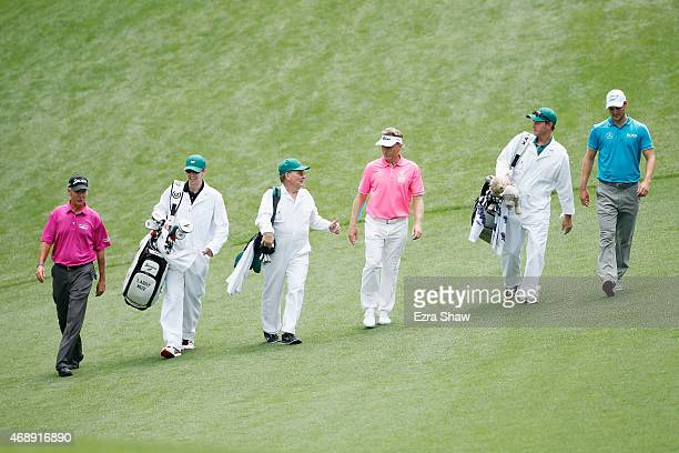 Larry Mize of the United States walks with Bernhard Langer and Martin Kaymer of Germany and their caddies during the Par 3 Contest prior to the start...