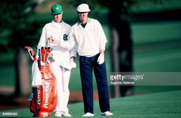 Larry Mize selects club while his caddie holds the golf bag during the 1993 Masters Tournament at Augusta National Golf Club on April 1993 in...