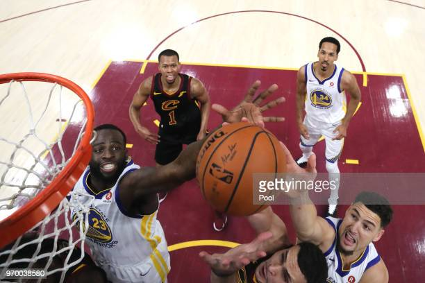 Larry Nance Jr #22 of the Cleveland Cavaliers competes for the ball with Draymond Green and Klay Thompson of the Golden State Warriors in the first...