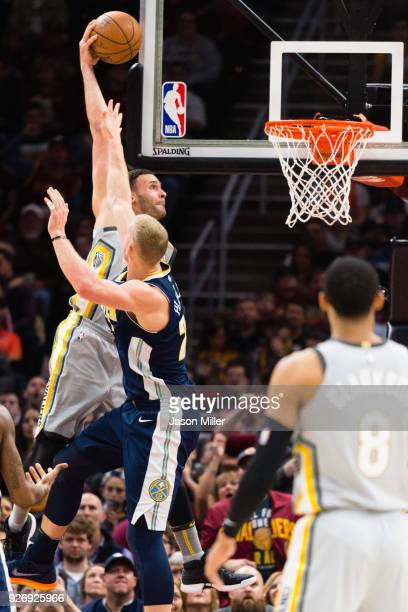 Larry Nance Jr #22 of the Cleveland Cavaliers dunks over Mason Plumlee of the Denver Nuggets during the first half at Quicken Loans Arena on March 3...