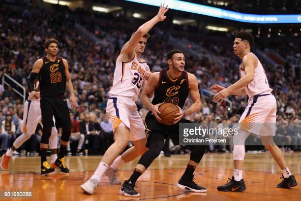 Larry Nance Jr #22 of the Cleveland Cavaliers handles the ball under pressure from Dragan Bender and Devin Booker of the Phoenix Suns during the...