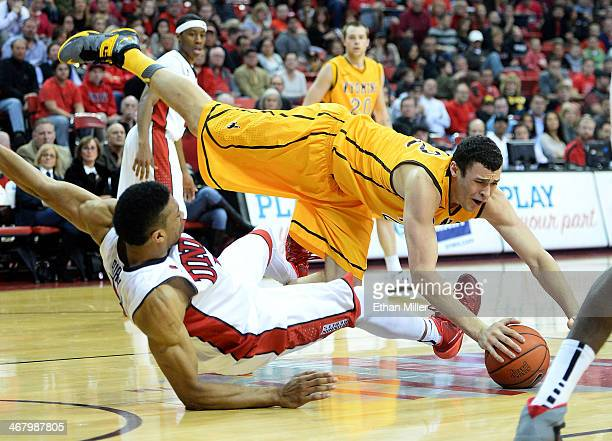 Larry Nance Jr #22 of the Wyoming Cowboys falls to the court after being fouled by Khem Birch of the UNLV Rebels during their game at the Thomas Mack...
