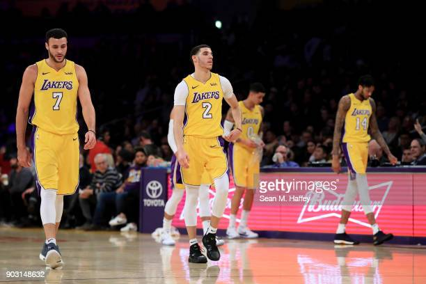 Larry Nance Jr #7 Lonzo Ball Kyle Kuzma and Brandon Ingram of the Los Angeles Lakers look on during the first half of a game against the Sacramento...