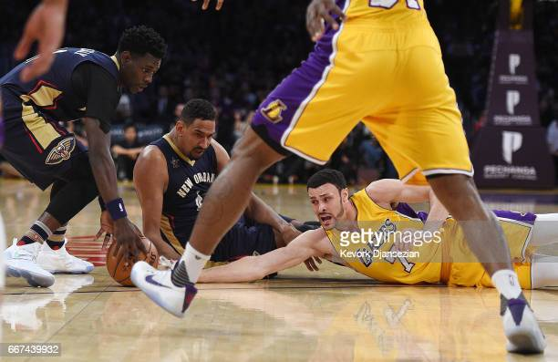 Larry Nance Jr #7 of the Los Angeles Lakers battle for the ball with Alexis Ajinca and Jrue Holiday of the New Orleans Pelican during the first half...