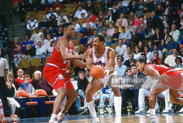 Larry Nance of the Cleveland Cavaliers looks to pass the ball by Rick Mahorn of the Philadelphia 76ers during an NBA basketball game circa 1990 at...
