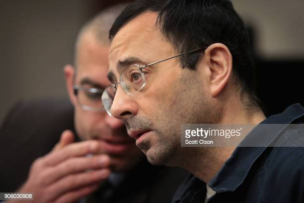 Larry Nassar speaks to attorney after arriving in court to listen to victim impact statements during his sentencing hearing after being accused of...