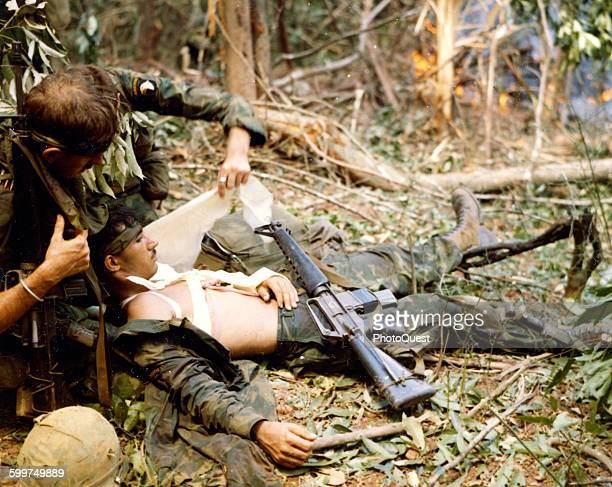 PFC Larry O Patriquine of the 101st Airborne is comforted by friends while waiting to be evacuated Mai Loc Viet Nam 1969