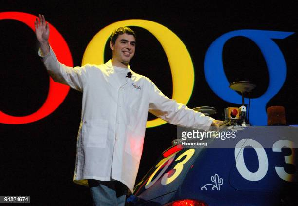 Larry Page Google Inc cofounder and president rides a robot car and waves as he makes his entrance to the Consumer Electronics Show keynote speech in...