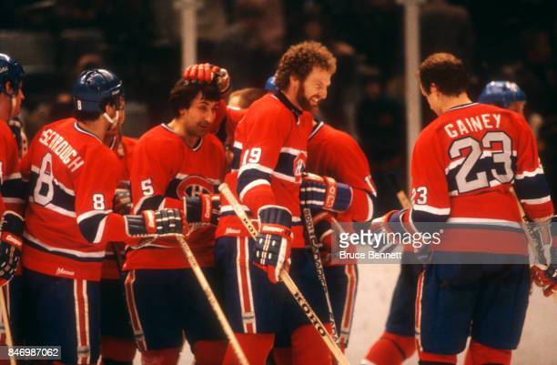 Larry Robinson and Bob Gainey celebrate with teammates on the ice after an NHL game circa 1979
