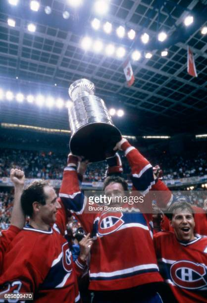 Larry Robinson Bob Gainey and Mats Naslund of the Montreal Candiens celebrate with the Stanley Cup Trophy after defeating the Calgary Flames in Game...