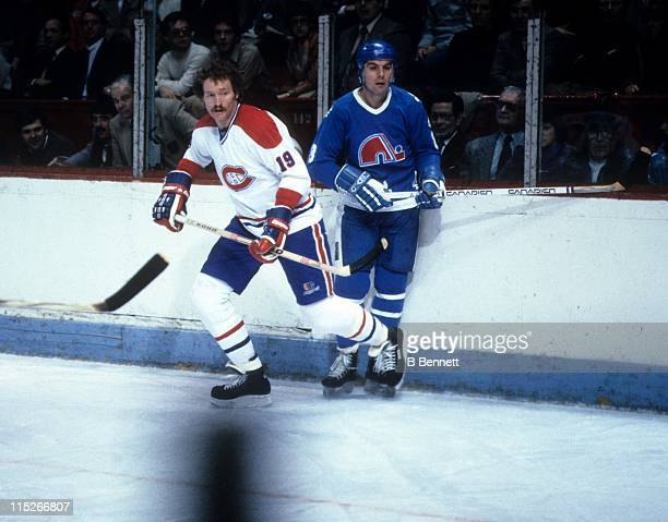 Larry Robinson of the Montreal Canadiens and Marc Tardif of the Quebec Nordiques skate on the ice during an NHL game circa 1981 at the Montreal Forum...