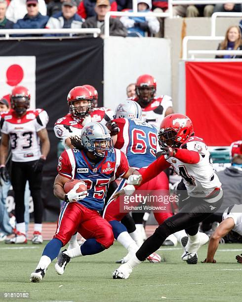 Larry Taylor of the Montreal Alouettes rushes with the ball while avoiding being tackled by Fernand Kashama of the Calgary Stampeders at Percival...
