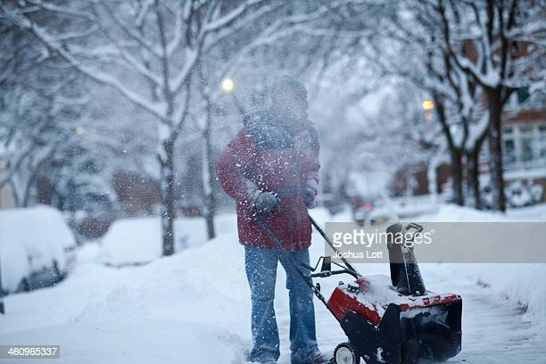 Larry Thomas snow blows several inches of snow from a sidewalk as the area deals with record breaking freezing weather January 6 2014 in Detroit...
