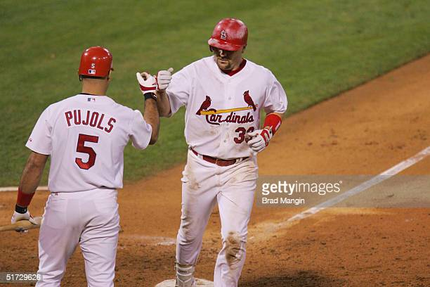 Larry Walker is congratulated by Albert Pujols of the St Louis Cardinals after hitting a home run in the ninth inning during game three of the 2004...