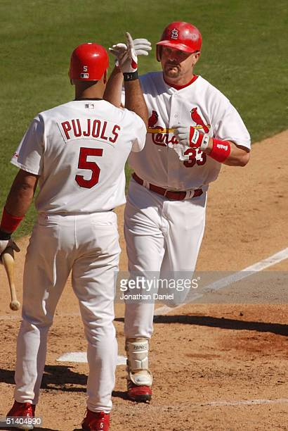 Larry Walker of the St Louis Cardinals is congratulated by teammate Albert Pujols after hitting a home run against the Los Angeles Dodgers in Game...