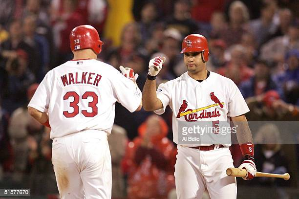 Larry Walker of the St Louis Cardinals is congratulated by teammate Albert Pujols after hitting a solo home run against the Boston Red Sox during the...