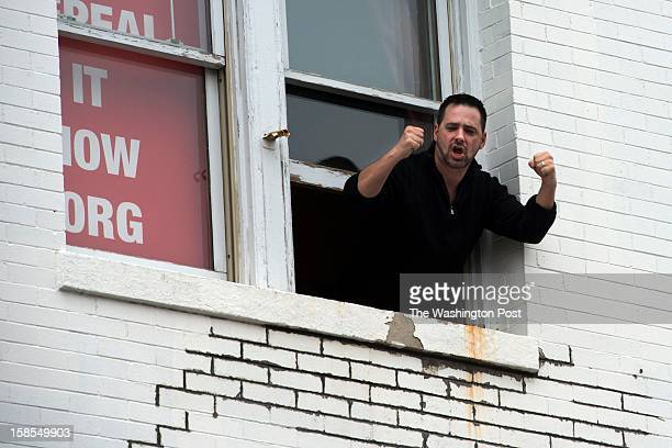 """Larry Ward yells """"Arm the teachers"""" as protestors rally past his office during the Emergency March on the NRA, organized by CREDO, in Washington, DC..."""