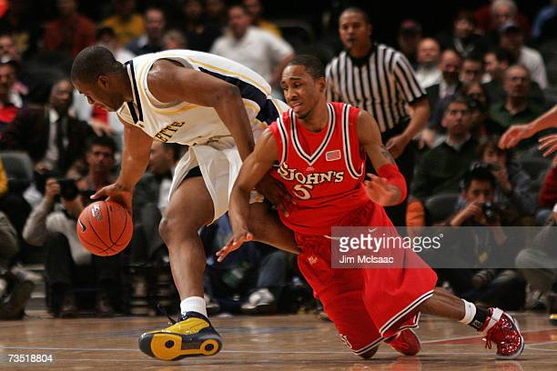 Larry Wright of the St Johns Red Storm fights for the ball with Dwight Burke of the Marquette Golden Eagles during the first round of the Big East...