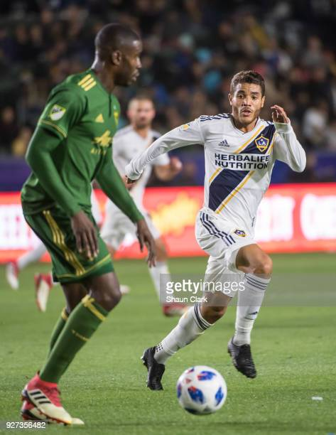 Larrys Mabiala of Portland Timbers has the ball as Jonathan dos Santos of Los Angeles Galaxy chases during the Los Angeles Galaxy's MLS match against...