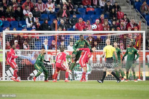 Larrys Mabiala of Portland Timbers heads clear while challenged by Aurelien Collin of New York Red Bulls during the New York Red Bulls Vs Portland...