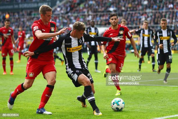 Lars Bender of Bayer 04 Leverkusen battles for the ball with Mickael Cuisance of Borussia Monchengladbach during the Bundesliga match between...