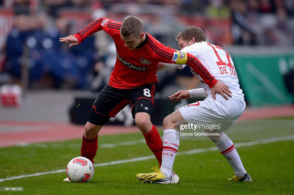 Lars Bender of Leverkusen is challenged by Marcel De Jong of Augsburg during the Bundesliga match between Bayer 04 Leverkusen and FC Augsburg at BayArena on February 16, 2013 in Leverkusen, Germany.