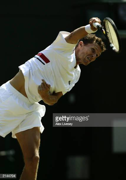 Lars Burgsmuller of Germany serves against Andre Agassi of the USA during day four of the Wimbledon Lawn Tennis Championships held on June 26 2003 at...