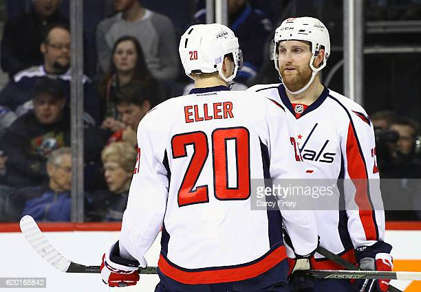 Lars Eller and Karl Alzner of the Washington Capitals discuss strategy during a first period stoppage in play against the Winnipeg Jets at the MTS...