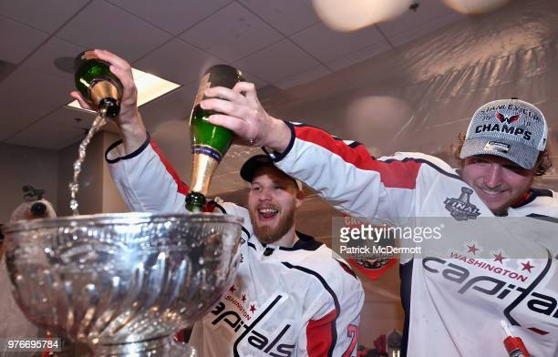 Lars Eller and Nicklas Backstrom of the Washington Capitals fill the Stanley Cup in the locker room after his team defeated the Vegas Golden Knights...