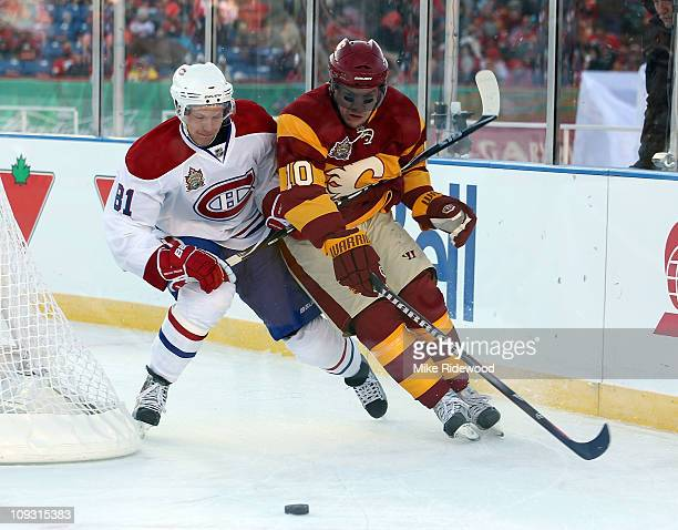 Lars Eller of the Montreal Canadiens and Niklas Hagman of the Calgary Flames battle during the 2011 NHL Heritage Classic Game at McMahon Stadium on...