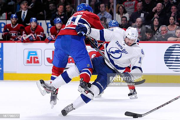 Lars Eller of the Montreal Canadiens body checks Alex Killorn of the Tampa Bay Lightning during the NHL game at the Bell Centre on November 12 2013...