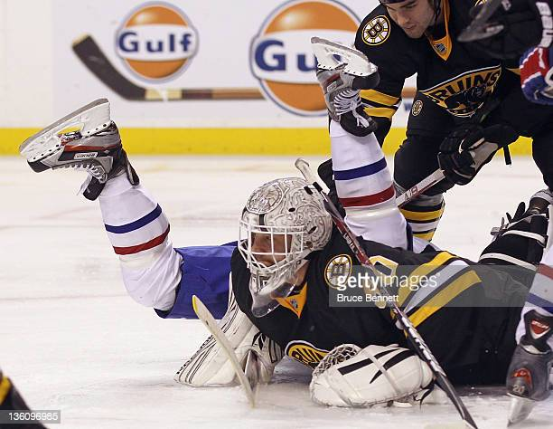 Lars Eller of the Montreal Canadiens flies over Tim Thomas of the Boston Bruins as Adam McQuaid stands guard at the TD Garden on December 19, 2011 in...
